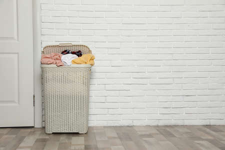 Plastic laundry basket full of dirty clothes near brick wall in room. Space for text Imagens - 124961282