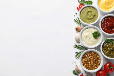 Composition with different sauces and ingredients on white background, flat lay. Space for text