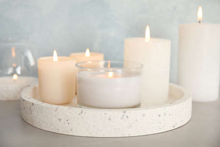 Tray with burning aromatic candles on table