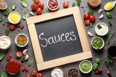 Small blackboard with word Sauces and different dressings on gray background, flat lay