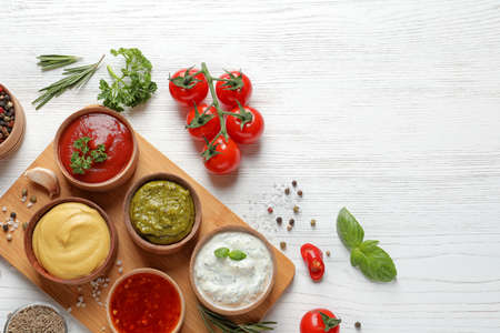 Flat lay composition with different sauces and space for text on white wooden background Stock Photo