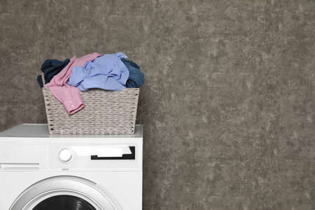 Wicker laundry basket full of dirty clothes on washing machine near color wall. Space for text Imagens - 124961384