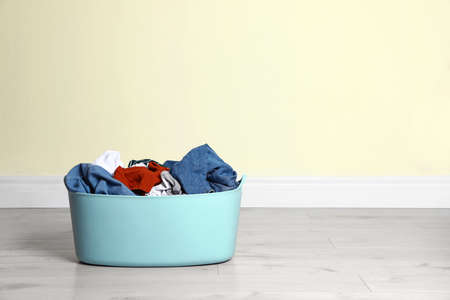 Plastic laundry basket full of dirty clothes on floor near color wall. Space for text Imagens - 124961398