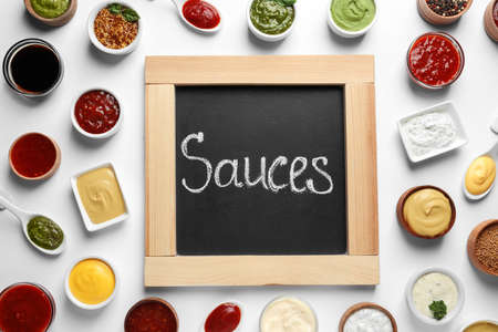 Small blackboard with word Sauces and different dressings on white background, flat lay