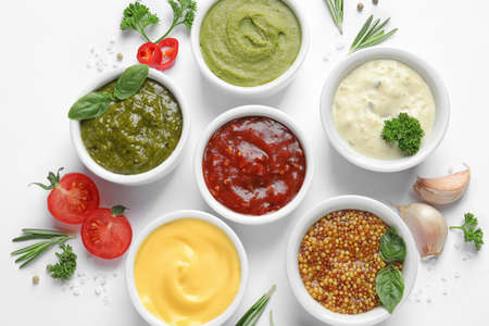 Composition with different sauces and ingredients on white background, flat lay