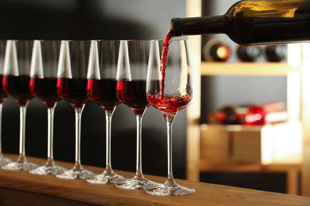 Pouring wine from bottle into glass in cellar