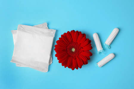 Different feminine hygiene products and flower on color background, flat lay. Gynecological care