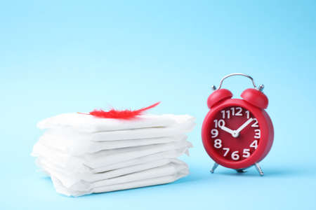 Packed menstrual pads with red feather and alarm clock on color background. Gynecological care