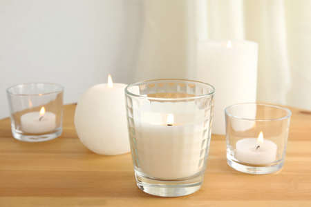 Different burning aromatic candles on wooden table