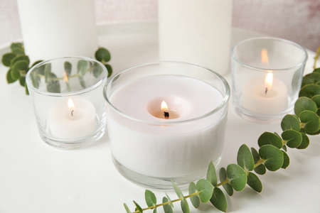 Composition with burning aromatic candles and eucalyptus on table Stock Photo