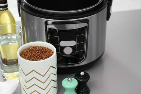 Modern multi cooker and ingredients on table, space for text