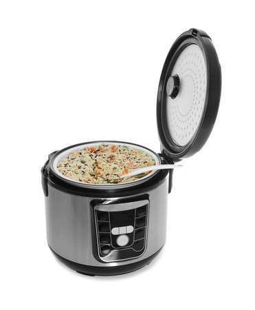 Delicious rice with vegetables and spoon in modern multi cooker on white background