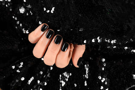 Woman with black manicure holding shiny fabric, closeup. Nail polish trends 写真素材