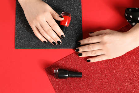 Woman with black manicure and nail polish bottles on color background, top view
