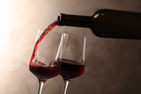 Pouring wine from bottle into glass on color background