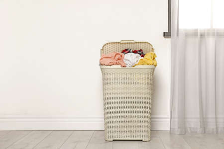 Plastic laundry basket full of dirty clothes on floor near light wall in room. Space for text Imagens - 124961900