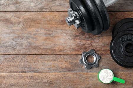 Flat lay composition with protein powder and dumbbell on wooden background. Space for text Stock Photo