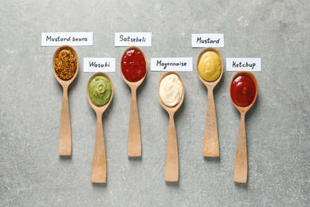 Different sauces in spoons and name tags on gray background, flat lay
