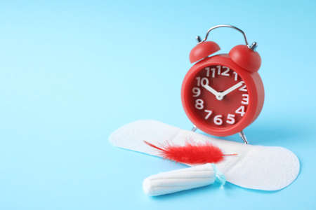 Different feminine hygiene products with red feather and alarm clock on color background, space for text. Gynecological care