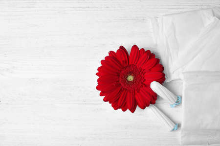 Different feminine hygiene products and flower on white wooden background, flat lay with space for text. Gynecological care