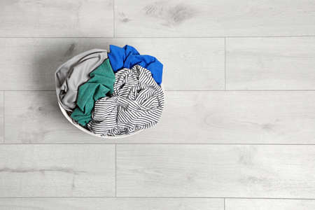 Laundry basket full of dirty clothes on floor, top view. Space for text Imagens