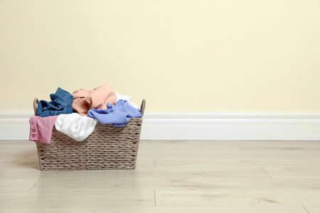 Wicker laundry basket full of dirty clothes on floor near color wall. Space for text Imagens - 124963041