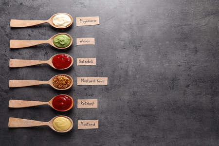 Different sauces in spoons and name tags on gray background, flat lay. Space for text Stock Photo - 124962760