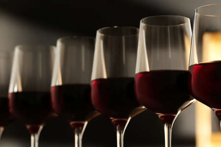 Glasses of red wine against blurred background, closeup. Expensive drink