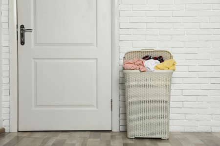 Plastic laundry basket full of dirty clothes near brick wall in room. Space for text Imagens - 124961977