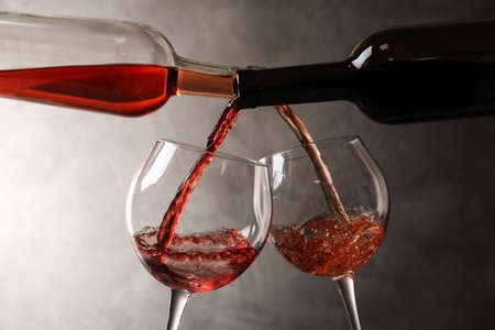 Pouring different wines from bottles into glasses on dark background 写真素材