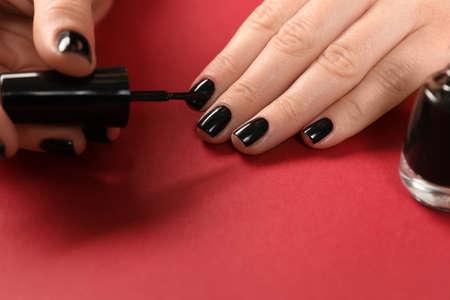 Woman applying black nail polish on color background, closeup