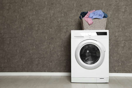 Wicker laundry basket full of dirty clothes on washing machine near color wall. Space for text Imagens - 124961989
