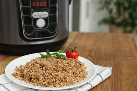 Plate with delicious buckwheat and multi cooker on wooden table. Space for text Imagens
