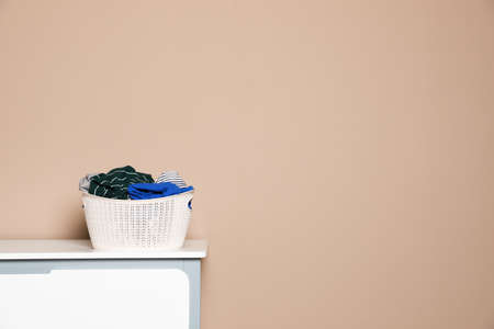 Plastic laundry basket with dirty clothes on chest of drawers near color wall. Space for text Imagens