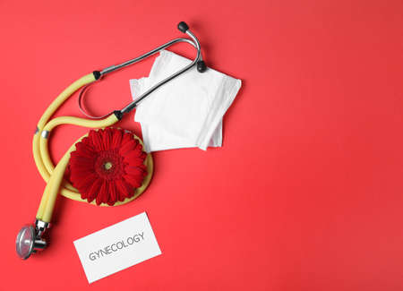 Card with word Gynecology, stethoscope, pads and flower on color background, flat lay. Space for text Stock Photo