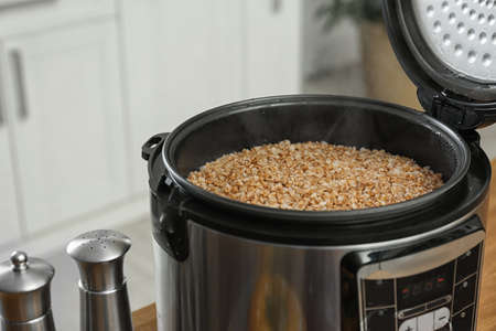 Modern multi cooker with delicious hot buckwheat in kitchen. Space for text Imagens