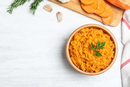 Flat lay composition with mashed sweet potatoes on wooden background, space for text