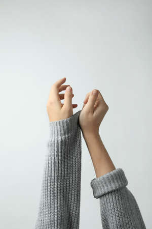 Woman taking off grey knitted sweater on light background, focus on hands