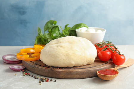 Fresh dough and ingredients for pizza on table against color background