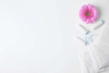 Different feminine hygiene products and flower on white background, top view with space for text. Gynecological care Stock Photo