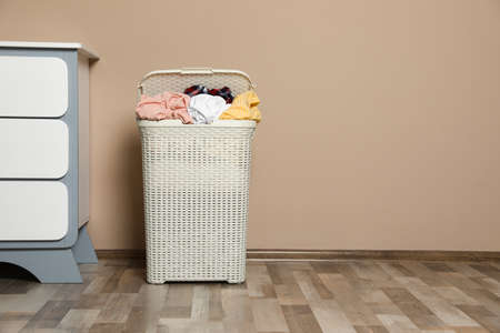 Plastic laundry basket with dirty clothes near color wall in room. Space for text Imagens - 124962197