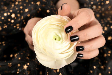 Woman with black manicure holding beautiful flower on dark background, closeup. Nail polish trends