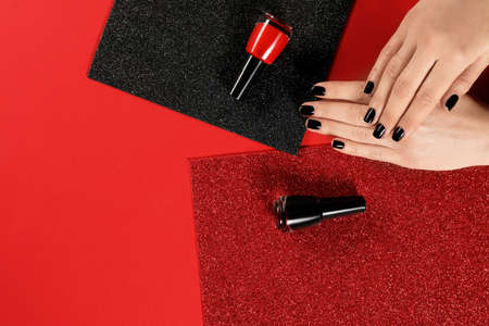 Woman with black manicure and nail polish bottles on color background, top view. Space for text