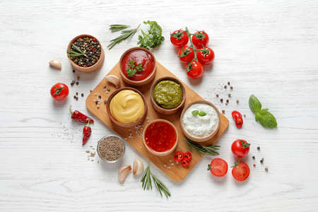 Flat lay composition with different sauces and ingredients on white wooden background Stock Photo