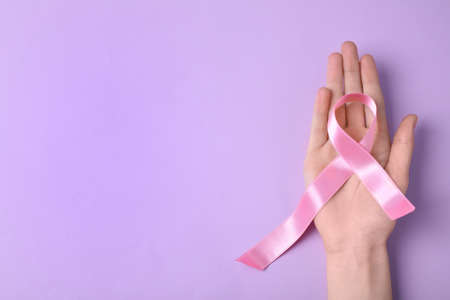 Woman with symbolic ribbon of breast cancer awareness and space for text on color background, top view. Gynecological care