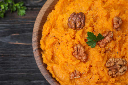 Bowl with mashed sweet potatoes on wooden table, closeup