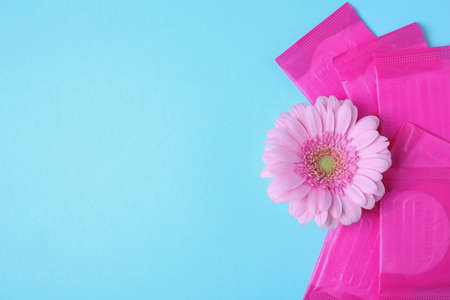 Packed menstrual pads and flower on color background, flat lay with space for text. Gynecological care