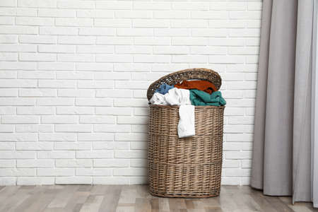 Wicker laundry basket full of dirty clothes near brick wall in room. Space for text Imagens - 124962481