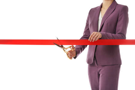 Woman in office suit cutting red ribbon isolated on white, closeup Фото со стока