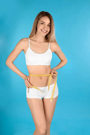 Slim woman measuring her waist on color background. Perfect body
